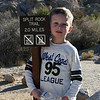 Kyle resting on the trailhead sign. He was a trooper and walked the entire way.